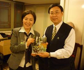行政院農業委員会林業試験所の黄裕星所長(右)に、自著『神の木』を手渡す李春子氏(左)